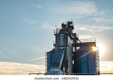 silver silos on agro manufacturing plant for processing drying cleaning and storage of agricultural products, flour, cereals and grain with beautiful clouds