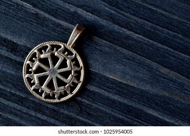 Silver Slavic symbol on the dark blue wooden background.