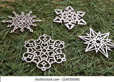 Silver snowflake ornaments on green pine branches background.  Winter christmas decoration lazer cut snowflakes on  pine branches.