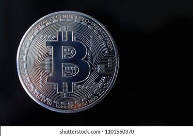 Silver souvenir coin Bitcoin on a black background.