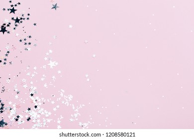 Silver sparkles, stars and glitters on pink background. Festive concept.