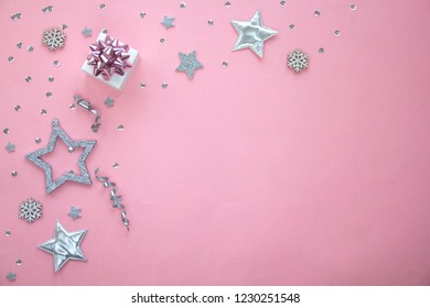 Silver sparkling christmas decoration on pastel pink background. Place for text. Festive concept. Concept of celebrating New year and Christmas. Flat lay style.