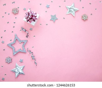 Silver sparkling christmas decoration on pastel pink background. Place for text. Festive concept. Flat lay style.