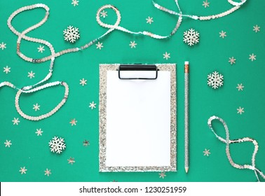Silver sparkling christmas decorations and notebook with wish list on green background, flat lay style. Concept of celebrating New year and Christmas.  2019 goals.