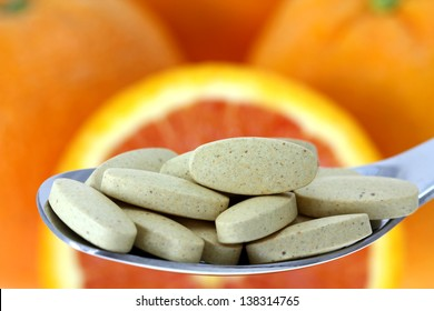 A silver spoon of film coated Vitamin C tablets with blurred background of fresh orange ideally representing excellent natural source of Vitamin C
