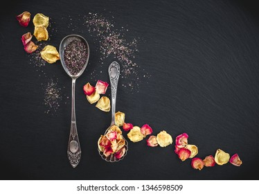 Silver spoons with floral tea and rose petals, on black slate background.