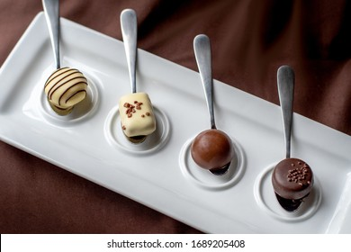Silver spoons hold a variety of decedent chocolates at this chocolate taste event