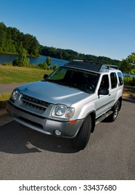 Silver Sports Utility Vehicle high angle lake view SUV