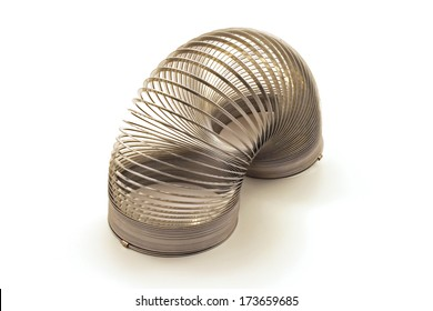 A silver spring coil toy against a white background
