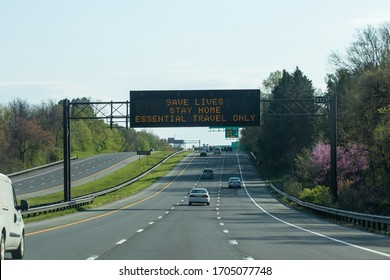 """Silver Spring, Maryland / USA - April 11, 2020: A sign above the highway says """"save lives, stay home."""" The message is the state's response to the COVID-19 pandemic and the stay-at-home order."""