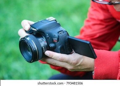 Silver Spring, MD - October 4, 2017: An amateur photographer holds a Canon Rebel T3i with a Canon 50mm f/1.4 lens.
