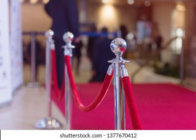 Silver stanchions with a red rope. Barrier, enclosed VIP area, protected enterance, private event, luxury gala concept.