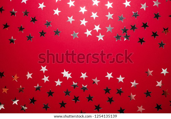 Silver star sprinkles on red backgound. Festive holiday confetti. Celebration concept. Top view, flat lay.