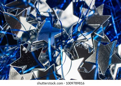 A lot of silver stars close-up with tinsel