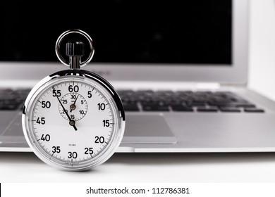Silver-Stopp-Uhr mit silbernem Laptop im Hintergrund