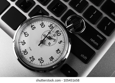 Silver stopwatch on silver laptop  keyboard closeup