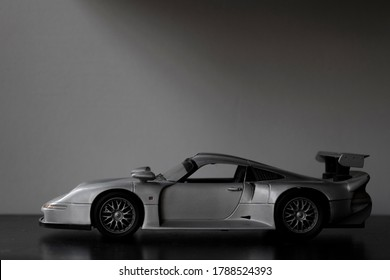 silver supercar toy on black table. Wall in the background.