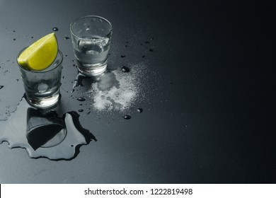 the silver tequila shot glasses, the lime slice and salt on the wet table