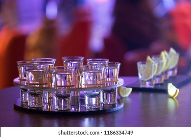 Silver tequila in a shot glasses tray on a wooden table bar background