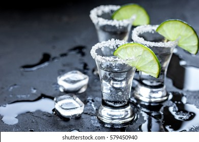 Silver tequila shots with ice and lime on black table background