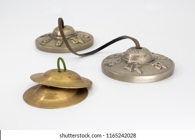 Silver Tibetan tingsha - two cymbals tied with a leather strap (Translation of the sanskrit symbols are Behold! The jewel in the lotus!) and Indian finger cymbals with green rubber handle
