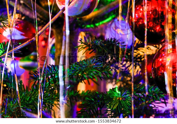 Silver tinsel on Christmas tree. Blured holiday background with garland, glass toys, balls, lights. Colorful decoration close-up.