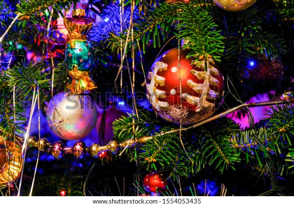 Silver tinsel on Christmas tree. Blured holiday background with garland, glass toys, balls, lights. Colorful decoration close up.