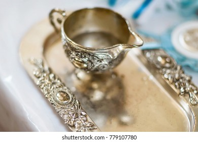 silver tray and jug with water accessories for baptism of the child in accordance with the church traditions
