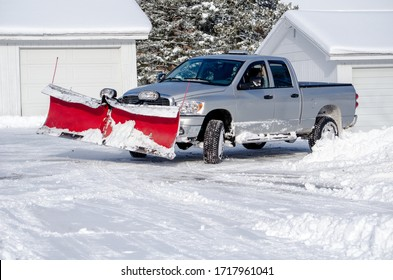 silver truck moving snow on a winter's day