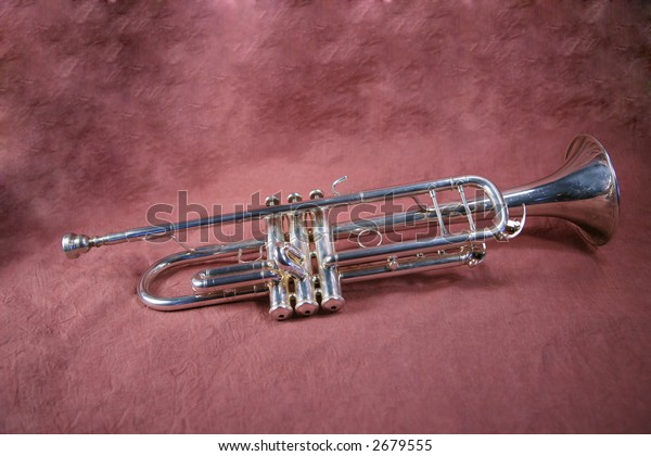 Silver trumpet on maroon background