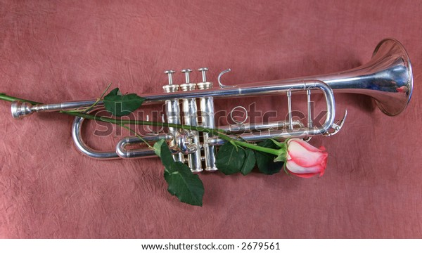 Silver trumpet and rose on maroon  background