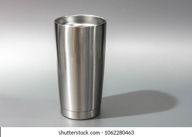 Silver tumbler glass cold store. Stainless steel thermos tumbler mug on gray  background.