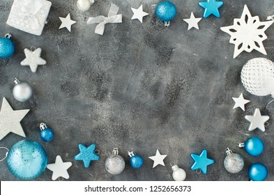 Silver and turquoise Christmas decorations on a grey background  top view