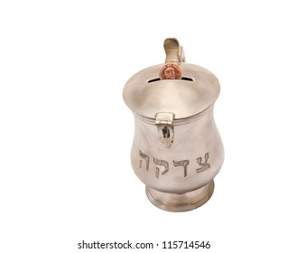 Silver tzedakah, or charity box with penny. Silver mug with a penny going into the coin slot isolated on a white background; horizontal view.