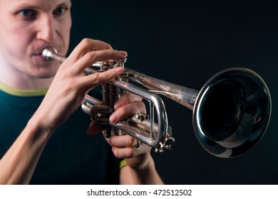 Silver vintage trumpet in the focus of the camera, the background with the face of man blowing in the tube is blurred. Accurate fingers of jazzman on the musical instrument.
