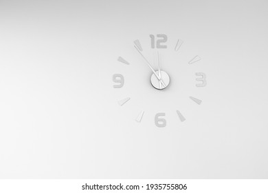A silver wall clock with arrows on a white wall shows the time of 11.55. The concept of time management, new year,