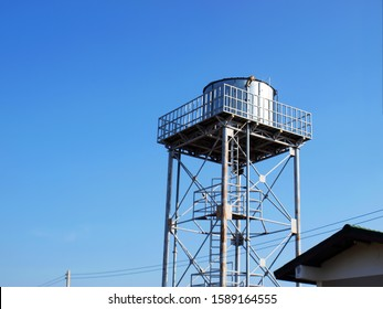 Silver water tank on the tower On a clean blue sky background With copy space