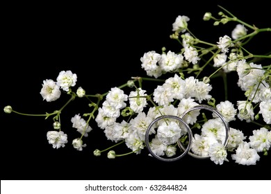 silver wedding rings in baby's breath isolated on black