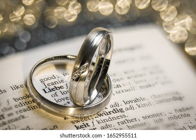 "Silver wedding rings frame the word ""Liebe"" for ""love"" in a lexicon, glittering bokeh in the background"