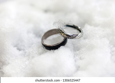 Silver wedding rings for her and him in winter time on the white snow