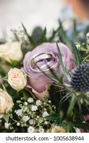 Silver wedding rings on flower bouquet with pink rose