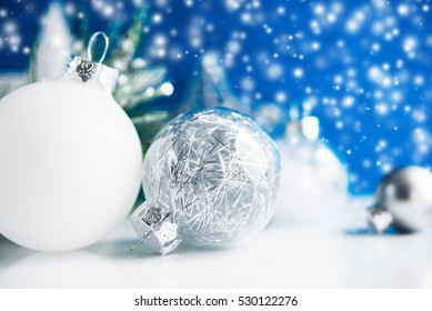 Silver and white christmas ornaments on blue bokeh background with blurred snow. Merry christmas card. Winter holiday snowing xmas theme. Happy New Year