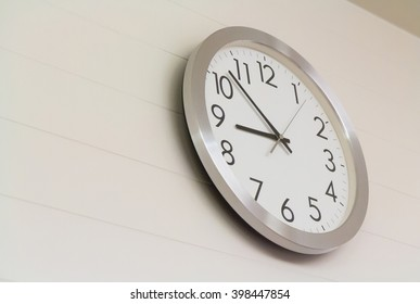 silver and white clock on white wooden wall concept : late morning, sleeping, morning