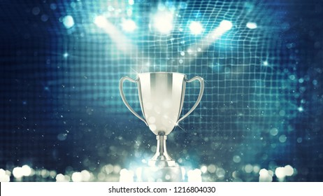 Silver winner s cup in the spotlight with soccer net background
