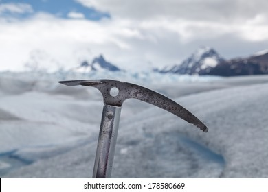 Silvered ice axe fixed on ice, with a glacier landscape background / Adventure Background
