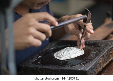 Silversmith using hammers and steel engraved  pattern on silver plate for accessory handmade