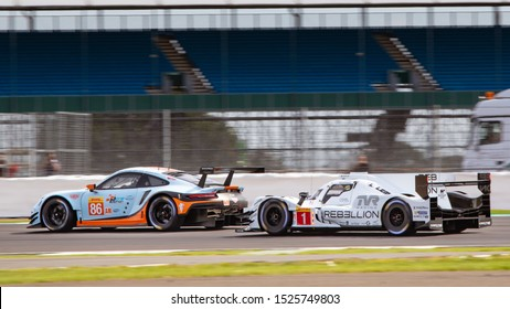 Silverstone Circuit, England, 29 Aug - 1 Sept 2019. Rebellion LMP1 car prepares to pass a Gulf Racing Porsche. WEC 4 Hours of Silverstone