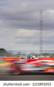 Silverstone Circuit, Northamptonshire, England, August 19 2018. #88 Dempsey-Proton Racing Porsche with blurred image of race car passing in opposite direction in foreground WEC 6 Hours of Silverstone.