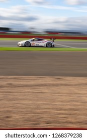 Silverstone Circuit, Northamptonshire, England, August 19 2018. #70 MR Racing Ferrari 488 LMGTE heads down Hangar Straight against a burred sky and large blurred foreground, WEC 6 Hours of Silverstone