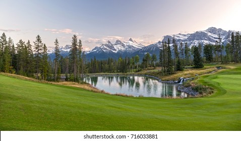 Silvertip Golf Course Green and Distant Landscape View of Three Sisters Snowy Mountain Tops above Town of Canmore in Foothills of Rocky Mountains Alberta Canada